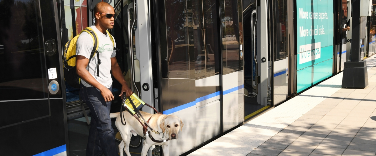 Student with seeing-eye dog exiting Lynx train